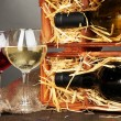 Wooden case with wine bottles and wineglasses on grey background — Stock Photo