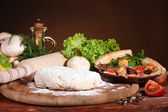 Delicious pizza dough, spices and vegetables on wooden table on brown background — Stock Photo