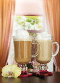 Fragrant coffee latte in glasses cups with vanilla pods, on table in cafe — Stock Photo