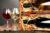 Dřevěné pouzdro s lahví vína a pohárky na šedém pozadí — Stock fotografie