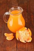 Full kannan av tangerine juice, på trä bakgrund — Stockfoto
