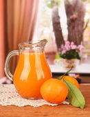 Full jug of tangerine juice, on wooden table on bright background — Stock Photo