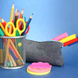 Pencil box with school equipment on blue background - Stock Photo