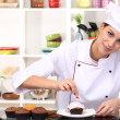 Young woman chef cooking cake in kitchen — Stock Photo