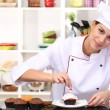 Young woman chef cooking cake in kitchen — Stock Photo #18750693