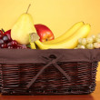 Wicker basket with fruits on color background — Stock Photo