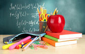 Back to school - blackboard with pencil-box and school equipment on table — Stock Photo
