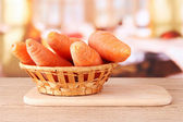 Carrots in basket on table in kitchen — Stock Photo