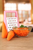 Carrots with grater on table in kitchen — Stock Photo