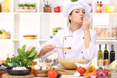Young woman chef cooking in kitchen — Stok fotoğraf