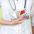 Close-up of female doctor hand holding pills, on color background - Stock Photo