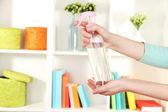 Sprayed air freshener in hand on white shelves background — Stock Photo