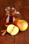 Full jug of apple juice and apple on wooden background — Stock Photo