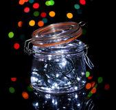 Christmas lights in glass bottle on blur lights background — Stock Photo