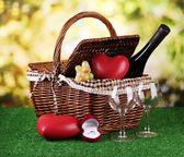 Picnic basket and bottle of wine on grass on bright background — Stock Photo