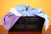 Bright clothes in laundry basket, on color background — Stock Photo