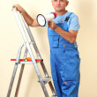 Foto Stock: Construction superintendent directs repair sitting on ladder