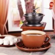 Cup of coffee with scarf and coffee mill on table in room - Stock fotografie