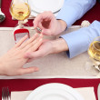 A man proposing and holding up an engagement ring over restaurant table - Stock Photo
