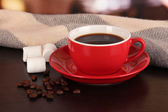 Cup of coffee with scarf on table in room — Stock Photo