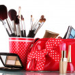 Red glass with brushes and makeup bag with cosmetics isolated on white — Stock Photo #18823571