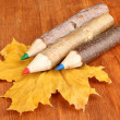 Colorful wooden pencils with autumn leafs on wooden table - Stock Photo