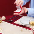 A man proposing and holding up an engagement ring over restaurant table - Foto Stock