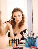 Jovem mulher bonita fazendo maquiagem perto de espelho — Fotografia Stock