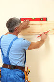 Builder measuring wall in room close-up — Стоковое фото