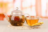 Exotic green tea with flowers in glass teapot on bright background — Stock Photo