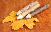 Kolorowe kredki drewniane z jesienią liście na drewnianym stole — Zdjęcie stockowe