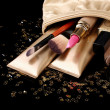 Stock Photo: Beautiful golden makeup bag and cosmetics isolated on black