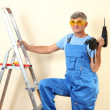 Handyman drill standing on ladder — Stock Photo