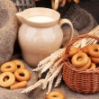Jar of milk, tasty bagels and spikelets on wooden background — Stock Photo