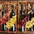 Wooden case with wine bottles on wooden table - Stock fotografie
