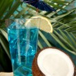 Blue Lagoon cocktail with coconut on tropical background — Stock Photo