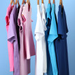 Variety of casual shirts on wooden hangers,on blue background - Stock Photo