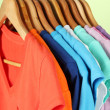 Variety of casual shirts on wooden hangers,on blue background — Stock Photo #18848427