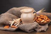 Jar of milk, tasty bagels and spikelets on wooden table, on grey background — Stock Photo