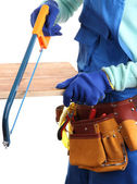 Male builder in blue overalls sawing board isolated on white — Stock Photo