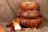 Milho cru, trigo e feijão em bacias de madeira na mesa no fundo do saco de carvão — Fotografia Stock