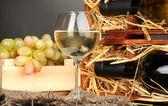ワイン ・ ボトル、ワイングラス、灰色の背景上の木製のテーブルでブドウの木製ケース — ストック写真