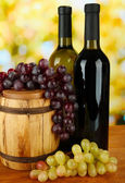 Composition of wine and grapes on wooden barrel on bright background — Stockfoto