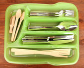 Green plastic cutlery tray with checked cutlery and wooden spoons on wooden table — Stock Photo