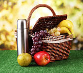 Picnic basket and thermos on grass on bright background — Stock Photo