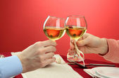 Hands of romantic couple toasting their wine glasses over a restaurant table — Stock Photo