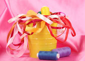 Color bucket with multicolor ribbons and thread on pink fabric background — Stock Photo
