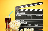 Movie clapperboard, cola and popcorn on orange background — Stock Photo