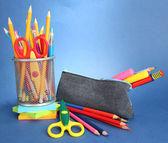 Estuche con material escolar sobre fondo azul — Foto de Stock
