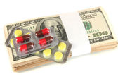 Pills and money isolated on white — Stock Photo